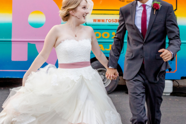 Newlyweds running in front of a food-truck at Sanctuary Event Space